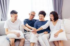 Famiglia asiatica con i bambini adulti ed i genitori senior che un le mani e che si siedono sul sofà a casa insieme Unit? della f immagine stock libera da diritti