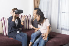 Famiglia asiatica felice a casa che indossa gli occhiali di protezione di realtà virtuale Fotografia Stock Libera da Diritti