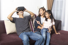 Famiglia asiatica felice a casa che indossa gli occhiali di protezione di realtà virtuale Fotografie Stock