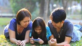 Famiglia asiatica felice che gioca insieme gioco in Smart Phone archivi video