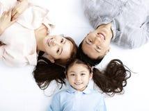 Famiglia asiatica felice che si trova sul pavimento immagine stock