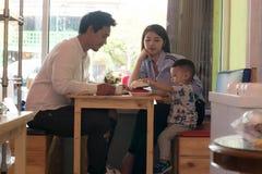 Famiglia asiatica felice, con un todler spendente insieme tempo dentro il deposito ed il caff? del forno mangiante dolce immagine stock libera da diritti