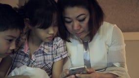 Famiglia asiatica felice divertendosi mentre giocando gioco sullo Smart Phone sul letto, in camera da letto archivi video