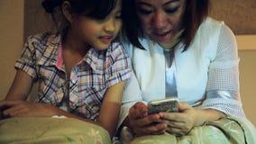 Famiglia asiatica felice divertendosi mentre giocando gioco sullo Smart Phone sul letto, in camera da letto video d archivio