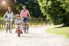 Famiglia asiatica sul giro del ciclo in campagna Fotografia Stock