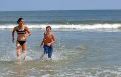 Famiglia attiva alla spiaggia Fotografie Stock Libere da Diritti