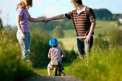 Famiglia attiva in estate che cammina e che va in bicicletta Immagini Stock