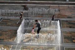 Famiglia australiana della gente che gioca in fontana al patio all'aperto fotografia stock libera da diritti