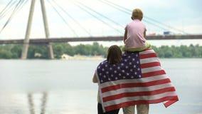Famiglia avvolta in bandiera americana che esamina ponte, immigrazione, festa dell'indipendenza archivi video