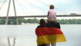 Famiglia avvolta in bandiera tedesca che esamina ponte, immigrazione, festa dell'indipendenza stock footage