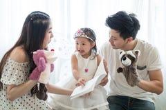 Famiglia, bambino e concetto domestico - genitori e bambina sorridenti Immagini Stock Libere da Diritti