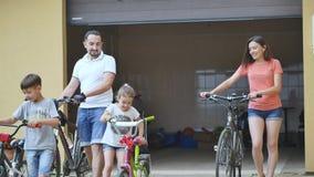 Famiglia in buona salute attraente che gode tenendo misura insieme ciclare all'aperto archivi video