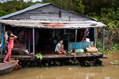 Famiglia cambogiana sulla casa galleggiante di legno della zattera Immagini Stock