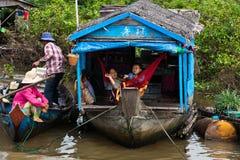 Famiglia cambogiana sulla casa galleggiante di legno della zattera Fotografie Stock Libere da Diritti