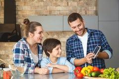 Famiglia a casa che sta insieme in app di sguardo curioso sorridente di rappresentazione del padre della madre e del figlio della fotografia stock libera da diritti