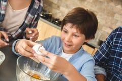 Famiglia a casa che sta insieme vicino alla tavola nel figlio della cucina che rompe il primo piano emozionante dell'uovo fotografia stock libera da diritti