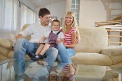 Famiglia a casa facendo uso del computer della compressa Immagine Stock
