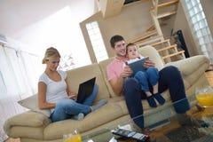 Famiglia a casa facendo uso del computer della compressa Immagine Stock Libera da Diritti