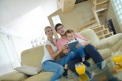 Famiglia a casa facendo uso del computer della compressa Immagini Stock