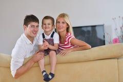 Famiglia a casa facendo uso del computer della compressa Fotografie Stock