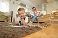 Famiglia a casa facendo uso del computer della compressa Fotografia Stock