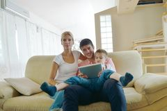 Famiglia a casa facendo uso del computer della compressa Fotografia Stock Libera da Diritti
