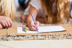 Famiglia a casa, i bambini che colorano sul pavimento immagini stock libere da diritti