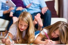 Famiglia a casa, i bambini che colorano sul pavimento fotografia stock
