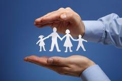 Famiglia a catena di carta protettiva in mani a coppa Fotografia Stock Libera da Diritti