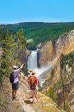 Famiglia che abbraccia e che gode di bella vista della cascata sull'escursione del viaggio nelle montagne Immagine Stock Libera da Diritti