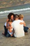 Famiglia che abbraccia sulla spiaggia Immagini Stock Libere da Diritti