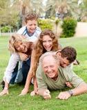 Famiglia che accatasta in su sul papà Fotografia Stock