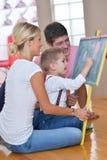 Famiglia che attinge consiglio scolastico a casa Fotografia Stock Libera da Diritti