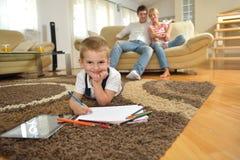 Famiglia che attinge consiglio scolastico a casa Fotografie Stock