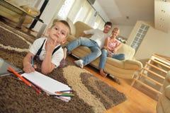 Famiglia che attinge consiglio scolastico a casa Immagini Stock Libere da Diritti