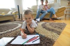 Famiglia che attinge consiglio scolastico a casa Fotografia Stock