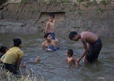 Famiglia che bagna nel fiume Immagini Stock