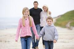 Famiglia che cammina alle mani della holding della spiaggia Fotografia Stock