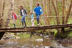 Famiglia che cammina attraverso il ponte di legno sopra la corrente in foresta Immagine Stock