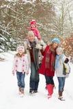 Famiglia che cammina attraverso il terreno boscoso dello Snowy Fotografia Stock