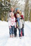 Famiglia che cammina attraverso il terreno boscoso dello Snowy Immagini Stock