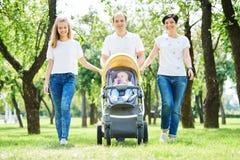 Famiglia che cammina con i bambini nel parco di estate Parenting felice immagini stock libere da diritti