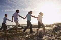 Famiglia che cammina congiuntamente sulla spiaggia Immagine Stock