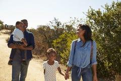 Famiglia che cammina insieme lungo la pista in campagna Immagini Stock