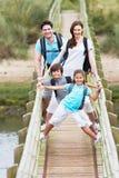 Famiglia che cammina lungo il ponte di legno Fotografia Stock Libera da Diritti