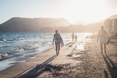 Famiglia che cammina lungo l'oceano nel tramonto fotografia stock libera da diritti