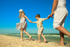 Famiglia che cammina lungo la spiaggia Fotografia Stock