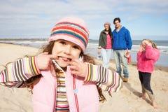 Famiglia che cammina lungo la spiaggia di inverno Immagini Stock