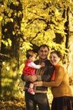 Famiglia che cammina nel parco di autunno Fotografia Stock