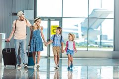 Famiglia che cammina nell'aeroporto fotografia stock